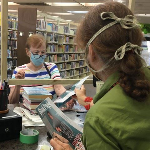 Masked patron borrowing books